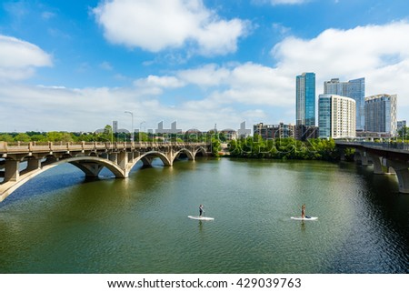 Austin, TX USA - April 14: Skyline view of the downtown area along the Colorado River with paddle boarders cruising by.