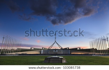 Australia Canberra acting as capital territory ACT Parliament building at sunset with illuminated facade and flagpoles - stock photo
