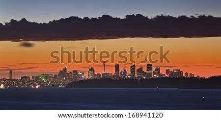 Australia capital city Sydney at sunset distant panoramic view under the cloudscape with the sky of different colour - stock photo
