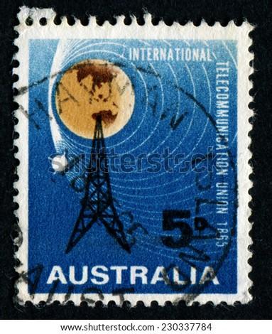 AUSTRALIA - CIRCA 1965: a stamp printed in the Australia shows Radio Mast and Satellite Orbiting Earth, Centenary of ITU, circa 1965 - stock photo