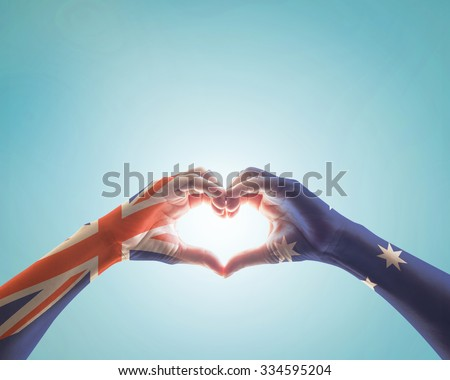 Australia flag pattern on people hands in heart shaped form on vintage style color tone sky background: Australia national public holiday celebration symbolic concept design idea: Remembrance day    - stock photo