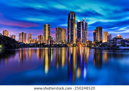Australia Gold coast Surfers paradise city towers reflecting in still waters of river at sunset - stock photo