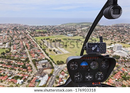 Australia Helicopter flight over SYdney residential areas and suburbs mid-air aerial view from cockpit with control dashboard  - stock photo