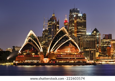 Australia iconic SYdney city landmarks CBD harbour and famous buildings greatly illuminated at sunset with reflection in still blurred harbour waters backgrounded by high-rises - stock photo