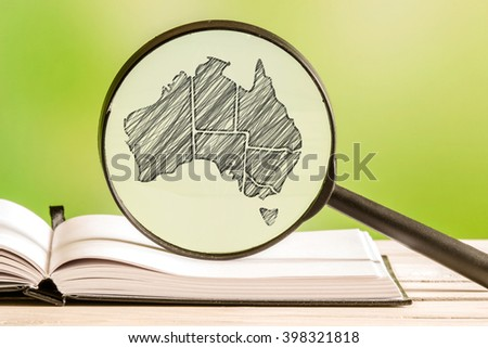 Australia information with a pencil drawing of a australian map in a magnifying glass - stock photo