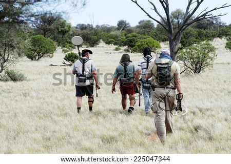 AUSTRALIA - MAY 6: Departure of a small group of gold miners equipped with metal detectors and picks at dawn looking for gold nuggets, may 6, 2007. - stock photo