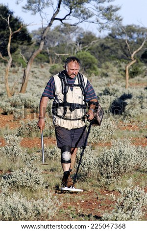 AUSTRALIA - MAY 10: Gold miner in the Australian outback prospecting area in the bush with his metal detector looking for gold nuggets, may 10, 2007. - stock photo