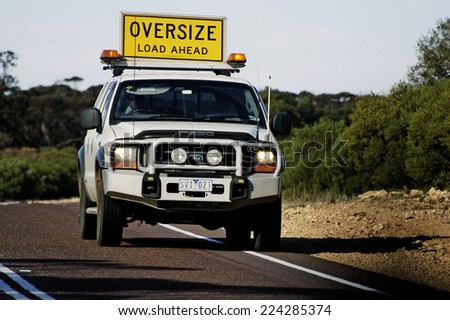 AUSTRALIA - MAY 20: Pilot car before a huge Australian truck to announce their arrival to other road users in Australia, may 20, 2007. - stock photo