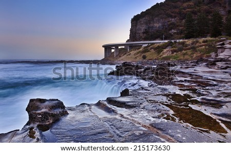 Australia NSW grand pacific drive sea cliff bridge at sunset low tide coastal seascape with sunlight and surfing waves - stock photo