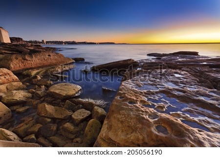 australia NSW manly beach in Sydney sunrise over sandstone coastline surfing waves and distant shore - stock photo