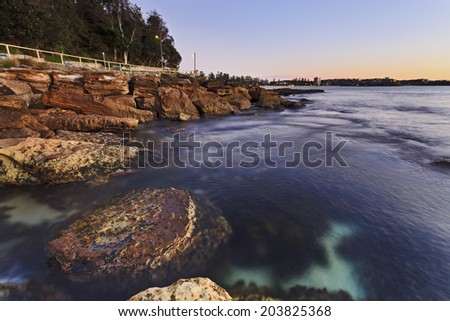 australia NSW manly ocean beach in Sydney sunrise over sandstone coastline surfing waves and distant shore - stock photo