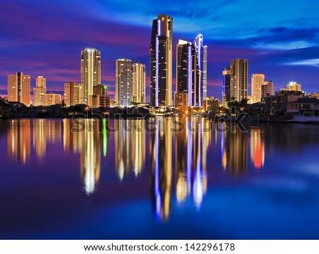 australia queensland gold coast surfers paradise tall hotel and apartment buildings skyscraper towers brightly illuminated at sunrise pink rising sun with still reflection in river - stock photo