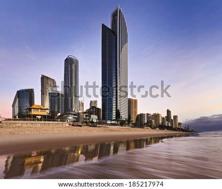 Australia Queensland SUrfers Paradise at Gold Coast CBD skyscrapers on the Beach at sunrise with waves surf and reflection on the sand - stock photo