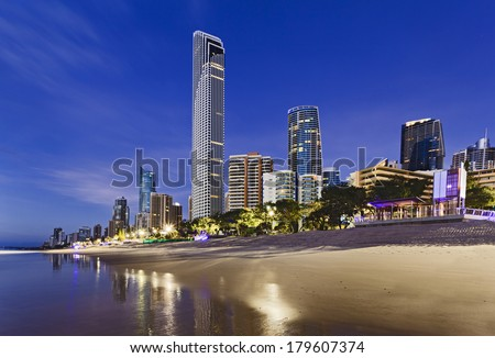 Australia Queensland Surfers Paradise CBD beach side at sunrise with reflection in ocean surf illuminated skyscrapers and Q1 - stock photo
