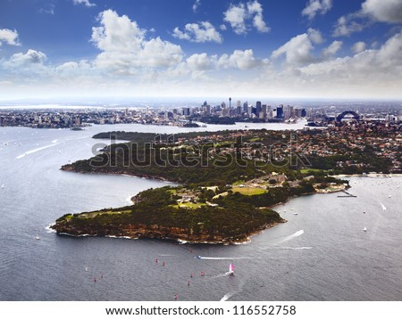 Australia Sydney aerial view over harbour, middle head towards city CBD and harbour bridge sunny day - stock photo