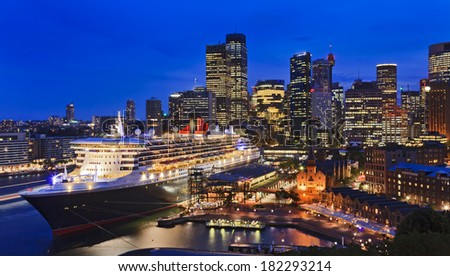Australia Sydney CBD at circular quay overseas passenger terminal docked cruise liner with skyscrapers in the background illuminated at sunset - stock photo