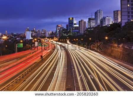 australia Sydney CBD view from over Cahill express way with lots of traffic at sunset with blurred lights - stock photo