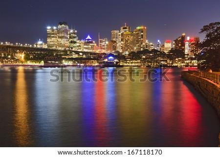 australia sydney CBD view over harbour waters at sunset with bright illuminated lights reflecting  - stock photo