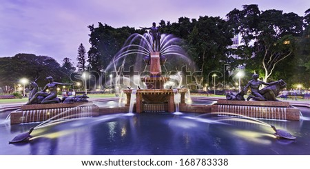 Australia Sydney central Hyde Park Archibald Fountain front wide panoramic view at sunset illuminated lights show - stock photo