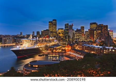 Australia Sydney Circular quay international seaport passenger terminal with docked ocean liner and city CBD in the background illuminated at sunset - stock photo