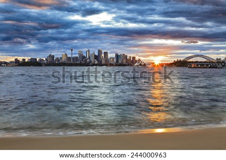 Australia Sydney city CBD and Harbour bridge landmarks at sunset with sun touching horizon and blurred harbour waves on sandy beach