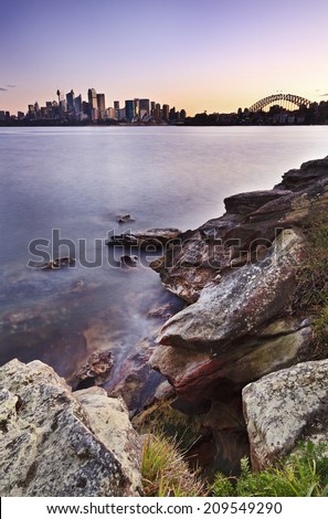 Australia Sydney city CBD and harbour bridge over harbour with sandstone rocks in foreground blurred waves at sunset - stock photo