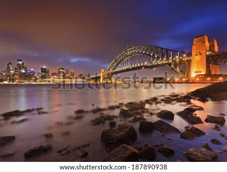 Australia Sydney city CBD and Harbour Bridge panorama from Kirribilli at low tide with sea rocks underneath and illuminated landmarks - stock photo