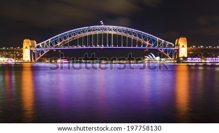 australia sydney city cbd harbour bridge side view after sunset vivid light show illumination and reflection in bay waters - stock photo