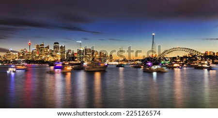 australia Sydney city CBD panoramic view of skyscrapers and harbour bridge from Cremorne point over sydney harbour at sunset with lots of boats and yachts anchored - stock photo