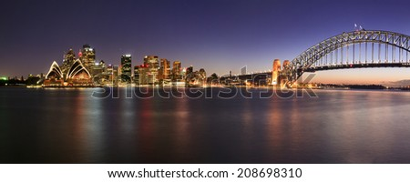 australia sydney city CBD panoramic view on main landmarks including harbour bridge at sunset bright illumination reflecting in still water - stock photo