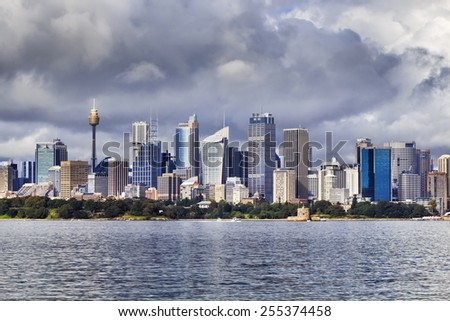 Australia Sydney City CBD skyscrapers over royal botanic garden across harbour waters at day time - stock photo