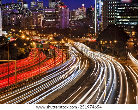 Australia SYdney city CBD with Harbour bridge at sunset with busy streets covered by cars at rush hour blurring headlights - stock photo