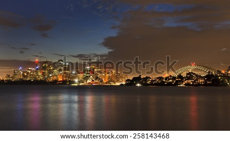 Australia Sydney city landmarks at dusk after sunset highly illuminated buildings with color reflection in blurred waters of Sydney Harbour - stock photo