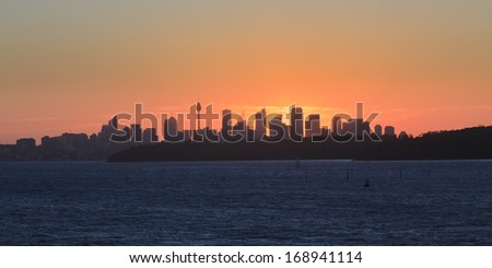 australia Sydney distant CBD panoramic view at sunset against orange sun and warm sky from South Head - stock photo