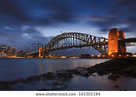 AUstralia Sydney harbour bridge side view at sunset illuminated lights under blurred cloudy sky during low tide time of sydney harbour water - stock photo
