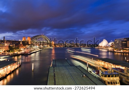 Australia Sydney major city landmark - circular quay at sunset view towards Harbour Bridge and passenger ferries - stock photo