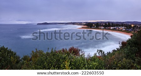 australia sydney northern beaches mona vale rock pool in a distant panoramic view from elevated lookout at sunset during high tide blurred surfing waves and sandy beach - stock photo