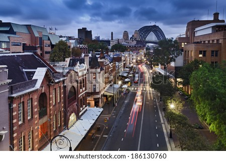 australia sydney the rocks historic district in the city view from top on george street illuminated houses and Sydney Bridge in the background at sunset - stock photo