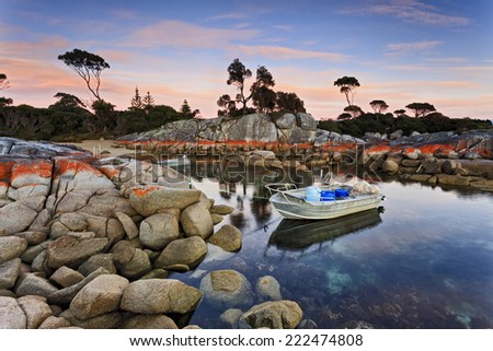 Australia Tasmania Bay of Fires Binalong bay quiet place with fishing boats anchored along red boulders at sunrise - stock photo