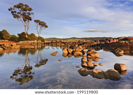 Australia Tasmania Bay of FIres still pacific ocean waters between boulders with red marks of bacteria reflecting at sunrise sunny morning - stock photo