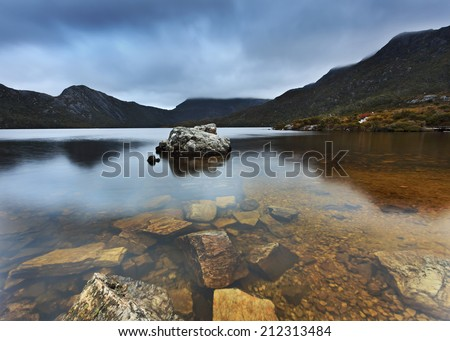 Australia Tasmania Cradle Mountain and DOve Lake national park bottom of the lake transparent pure water and stones within still reflection - stock photo