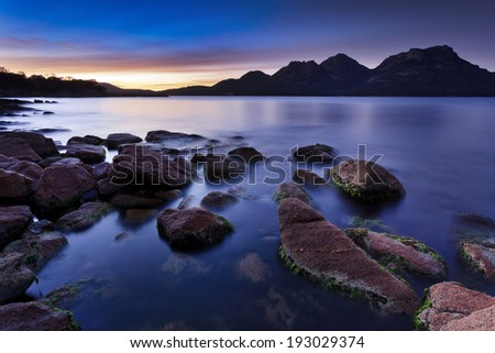 AUstralia Tasmania Freycinet National park coles bay rocky coastline at sunrise with granite boulders standing out sea water surf and tide against raising sun - stock photo
