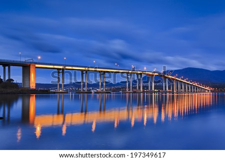 Australia Tasmania Hobart Tasman bridge over Derwent river at sunrise illuminated full length side view cloudy morning with Hobart city and Mt Wellington in the background