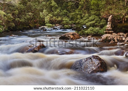 australia Tasmania St Clair lake national park watersmeet point water rivers meet blurred current over stones and boulders with aboriginal stone sign - stock photo