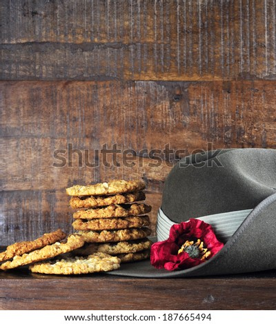 Australian army slouch hat and traditional Anzac biscuits on dark recycled wood with remembrance red poppy for Anzac Day or Remembrance Armistice Day. - stock photo