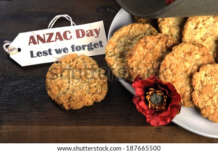 Australian army slouch hat and traditional Anzac biscuits on dark recycled wood with remembrance red poppy with Anzac Day, Lest We Forget tag. - stock photo