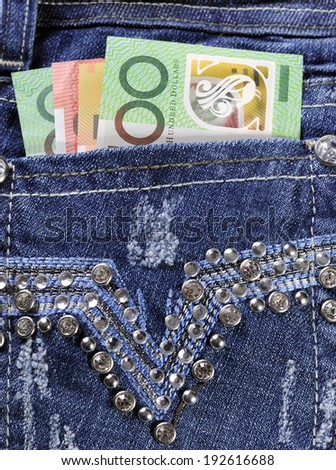 Australian hundred, fifty and twenty dollar notes in back pocket of feminine ladies rhinestone decorated jeans, for money in the pocket concept image, close up. - stock photo