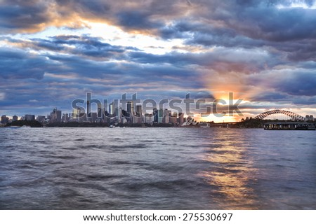 Australian landmarks of Sydney - cityscape, harbour and bridge at sunset with setting sun touching horizon behind skyscrapers