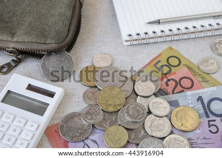 Australian money, AUD with calculator, notebook and small money pouch,selective focus on 1 dollar coin - stock photo