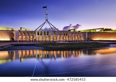 Australian national parliament house in Canberra. Facade of the building brightly illuminated and reflecting in blurred water of fountain pond under waving national flag on flagpole at sunset.